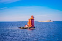 Outdoor view of the red lighthouse on the Norwegian sea over a rock. In a gorgeous blue sky in Hurtigruten Norway Royalty Free Stock Images