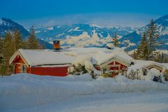 Outdoor view of red wooden typical housecovered with snow in the roof in GOL. Norway royalty free stock photo