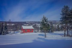 Outdoor view of red wooden typical housecovered with snow in the roof in GOL. Norway royalty free stock images