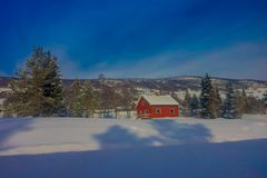 Outdoor view of red wooden typical housecovered with snow in the roof in GOL. Norway stock photography