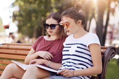 Outdoor view of serious concentrated two schoolgirls reads textbook attentively, try to learm material for lesson, enjoy fresh air stock photography