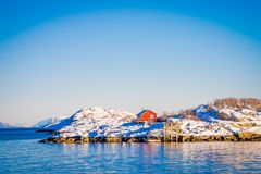 Outdoor view of a single red house over a rocky land in Henningsvaer on Lofoten islands. In Norway Stock Image