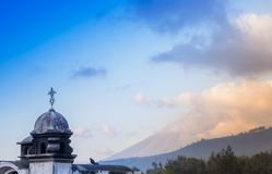 Outdoor view of stoned dome of building in Antigua city with agua volcano mountain behind in a gorgeous sunny day and. Blue sky in Antigua city in Guatemala Stock Image