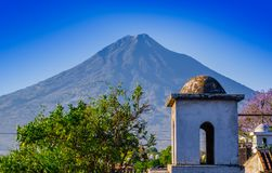 Outdoor view of stoned dome of building in Antigua city with agua volcano mountain behind in a gorgeous sunny day and. Blue sky in Antigua city in Guatemala Royalty Free Stock Photos