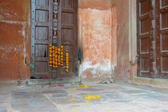 Outdoor view of a wooden door with some yellow flowers hanging, in a old house, in Agra city near of Taj Mahal in India Royalty Free Stock Photos