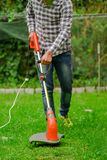 Outdoor view of young worker using a lawn trimmer mower cutting grass in a blurred nature background.  Stock Images