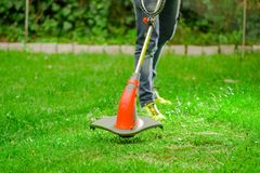 Outdoor view of young worker wearing jeans and using a lawn trimmer mower cutting grass in a blurred nature background.  Royalty Free Stock Photos
