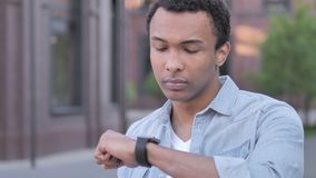 Outdoor Waiting African Man Watching Time on Wristwatch. 4k high quality, 4k high quality stock footage