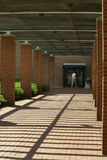 Outdoor Walkway. Semi-covered outdoor walkway with converging lines- a college student is at the end, walking into a doorway Stock Image