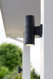Outdoor wall lamp. Black outdoor wall lamp on pole Royalty Free Stock Image