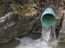 Outdoor water drainage pipe. With water flowing into a pool surrounded by rocks Stock Photography