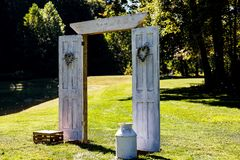 An Outdoor Wedding Arbor prepared for a rustic wedding. Decorated and arranged to allow for beautiful pictures from both front and back during the ceremony stock photography