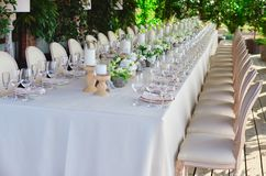 Outdoor wedding celebration at a restaurant. Festive table setting, catering. Wedding in rustic style in summer. Beautiful small bouquets on a table. selected Stock Image