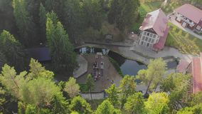 Aerial top view of wedding ceremony with arch and guests sitting on chairs, on the riverside stock footage
