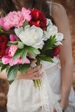 Outdoor wedding ceremony, close up of stylish bride with wedding bouquet of flowers stock photo