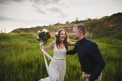 Outdoor wedding ceremony, stylish happy smiling groom and bride are laughing and looking at each other in the green field royalty free stock photos