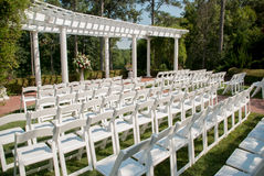 Outdoor Wedding Set up. White foldable chairs are set in rows in front of a pergola for an outdoor summer wedding stock photography