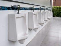 Outdoor white ceramic urinals men public toilet. Row of outdoor white ceramic urinals men public toilet,Closeup white urinals Stock Photo