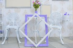 Outdoor white iron furniture and empty picture frames with purple accents stock image