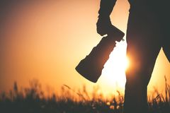 Outdoor Wildlife Photographer. Safari Outdoor Photographer at Sunset. Silhouette of Men Keeping Digital Camera in Hand with Large Telephoto Lens For the Better Royalty Free Stock Images