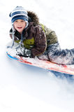 Outdoor winter activitiy. Young boy tobogganing down a snowy hill Stock Images