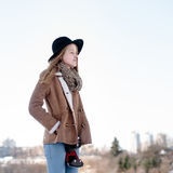Outdoor winter lifestyle portrait of pretty blonde woman with retro camera Royalty Free Stock Photos