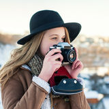 Outdoor winter lifestyle portrait of pretty blonde woman with retro camera Royalty Free Stock Photo