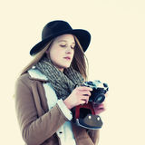 Outdoor winter lifestyle portrait of pretty blonde woman with retro camera Royalty Free Stock Photography