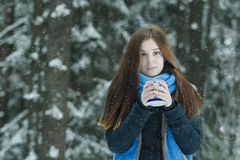 Outdoor winter portrait of freezing young lady holding cup with hot drink during heavy snowfall in conifer forest Royalty Free Stock Image