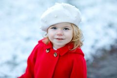 Outdoor winter portrait of little cute toddler girl in red coat and white fashion hat barret. Healthy happy baby child. Walking in the park on cold day with royalty free stock photography