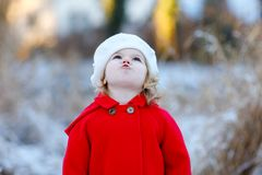 Outdoor winter portrait of little cute toddler girl in red coat and white fashion hat barret. Healthy happy baby child. Walking in the park on cold day with stock photo