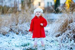 Outdoor winter portrait of little cute toddler girl in red coat and white fashion hat barret. Healthy happy baby child. Walking in the park on cold day with royalty free stock image
