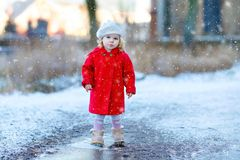 Outdoor winter portrait of little cute toddler girl in red coat and white fashion hat barret. Healthy happy baby child. Walking in the park on cold day with stock photography