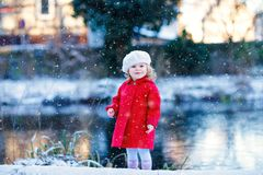 Outdoor winter portrait of little cute toddler girl in red coat and white fashion hat barret. Healthy happy baby child. Walking in the park on cold day with royalty free stock photos