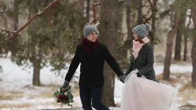 Outdoor winter shot of young wedding couple running and having fun holding hands in snow weather pine forest during. Snowfall stock video