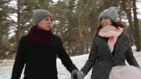 Outdoor winter shot of young wedding couple running and having fun holding hands in snow weather pine forest during. Snowfall stock video footage