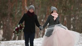 Outdoor winter shot of young wedding couple running and having fun holding hands in snow weather pine forest during. Snowfall stock footage