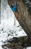 Outdoor winter sport. Rock climber ascending a challenging cliff. Extreme sport climbing. Stock Photography