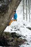 Outdoor winter sport. Rock climber ascending a challenging cliff. Extreme sport climbing. Royalty Free Stock Image