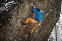 Outdoor winter sport. Rock climber ascending a challenging cliff. Extreme sport climbing. Stock Image