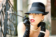 Outdoor woman portrait, smoking a cigarette with cigarette holder, dressed in hat and pearl jewelry Stock Image