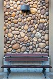 Outdoor Wood Bench by Rock Wall with light sconce. Outdoor garden wood bench on pavement by river stone rock wall with light sconce background closeup detail Stock Image
