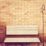 Outdoor wooden chair on brick wall Royalty Free Stock Photography