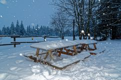 Outdoor wooden garden table while snowfall. Scenic view of the winter landscape while snowfall with outdoor garden table in foreground and forest in the royalty free stock photos
