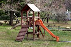 Outdoor wooden public playground equipment with climbing steps and slide stock photo