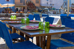 Outdoor wooden table set for dinner Stock Photos
