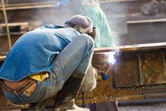 Outdoor worker with protective mask welding metal and sparks. At thailand Royalty Free Stock Image