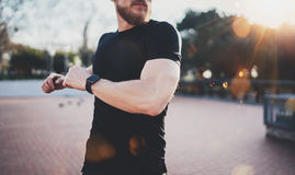 Outdoor Workout lifestyle concept.Young man stretching his body muscles before training.Muscular athlete wearing smart Stock Image
