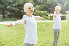 Nice aged woman exercising. Outdoor workout. Nice positive aged women standing on the grass and smiling while exercising outdoors Stock Photography