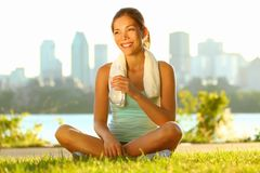 Outdoor workout woman. Fitness woman runner relaxing drinking water after training outside in city park with skyline in background. Beautiful young multiracial Stock Photos